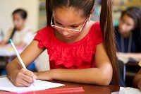 A girl at a desk writing with pencil and paper