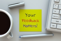 "A note on a desktop reads ""Your Feedback Matters!"""