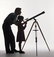 image of father and daughter looking through a telescope